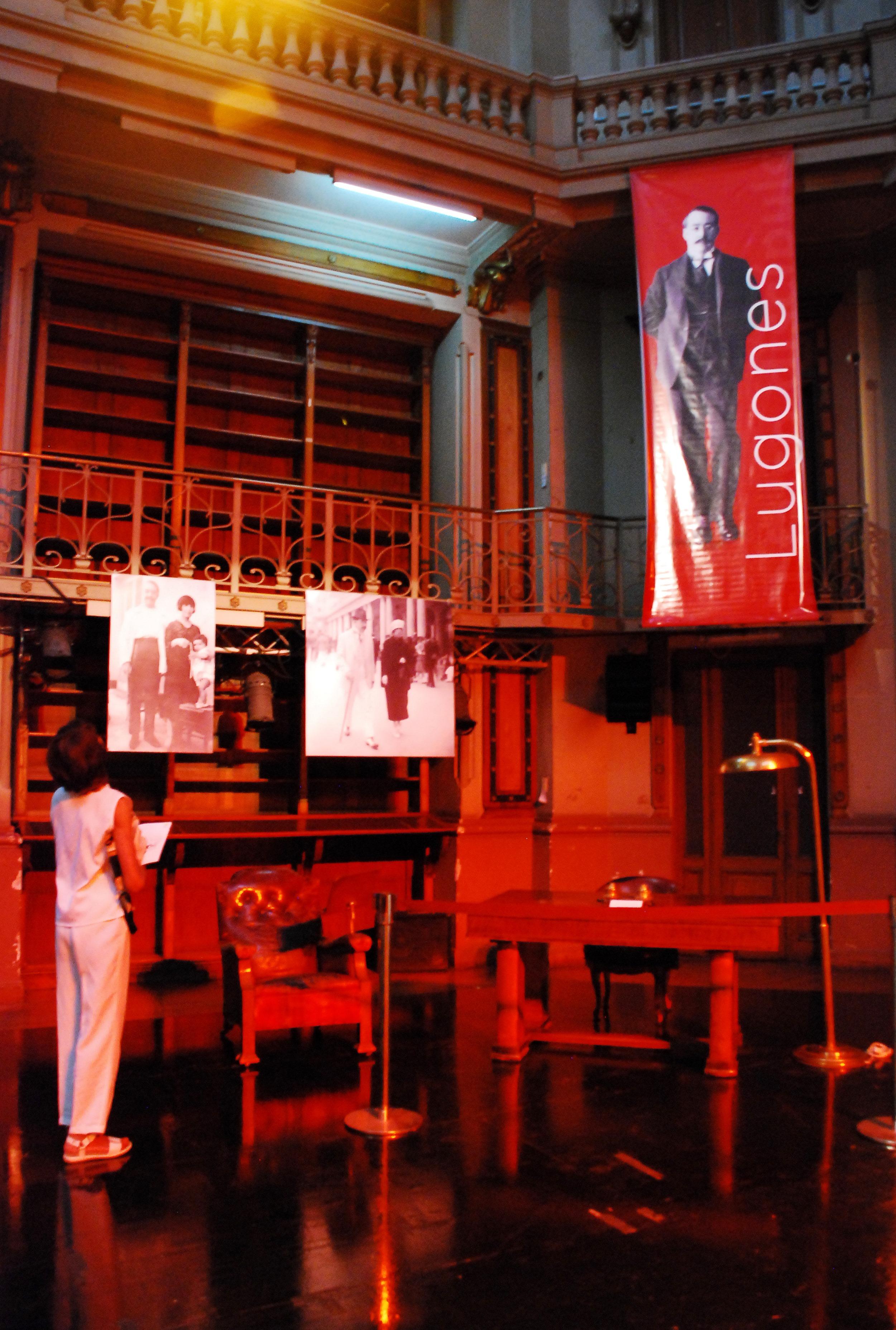 Fotografía de la exposición realizada con motivos del 80 aniversario del fallecimiento de Leopoldo Lugones. Muestra el escritorio del escritor, el sillón, fotos y una persona mirando la exposición.