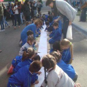 Alumnos de nivel inicial interviniendo un rollo de 100 metros de papel